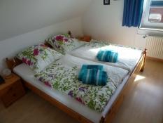 Wohnung 2, helles Schlafzimmer mit Bettwäsche und Handtüchern