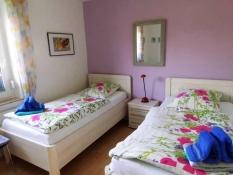Fewo 1 in Ferienwohnungen Kolks Huus in Neuharlingersiel an der Nordsee, Zweites Schlafzimmer mit 2 hohem komfortablen Einzelbetten, Fenster mit Rollläden, Plissees und Insektenschutz